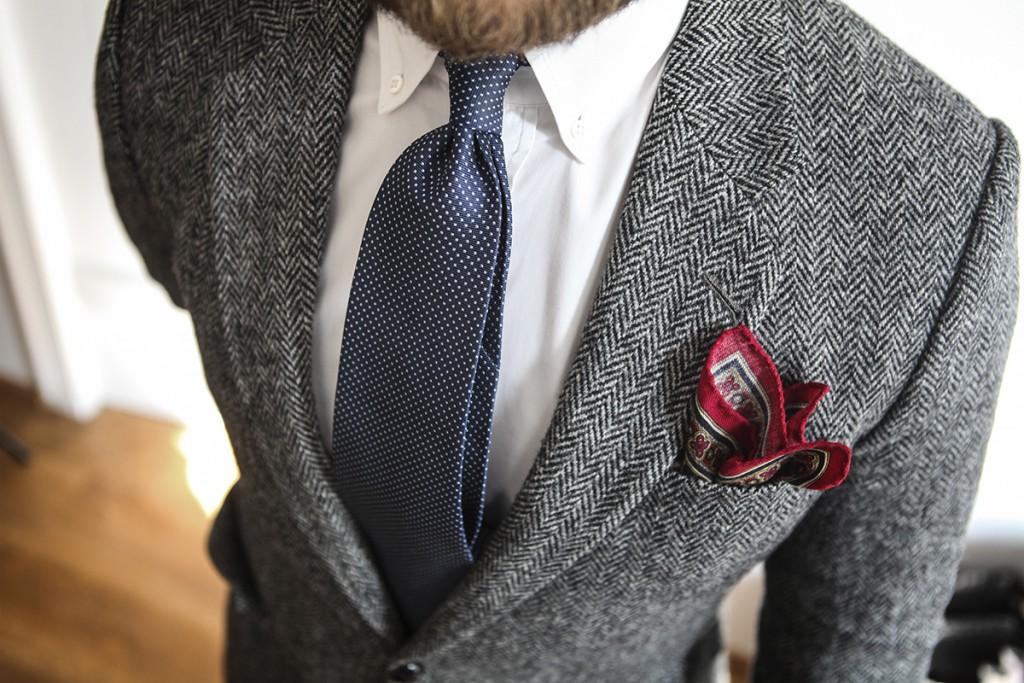poszetka z bordowymi brzegami, szary garnitur w jodełkę, granatowy krawat i koszula bd