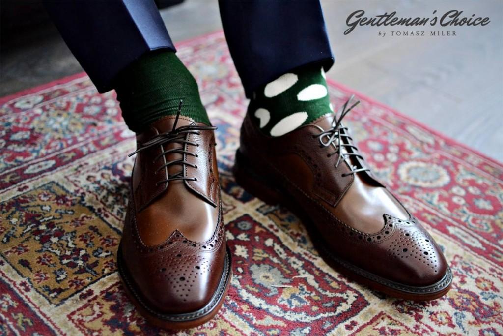 zielone skarpety w elipsy, brązowe buty i granatowe nogawki
