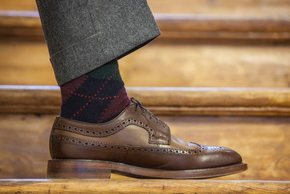 skarpeta w kratę, brązowy but i szara nogawka