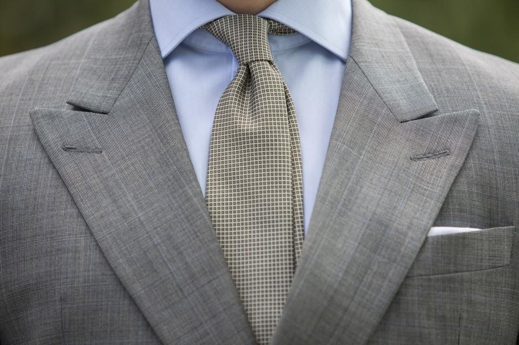 krawat w drobną kratę, błękitna koszula i szara marynarka
