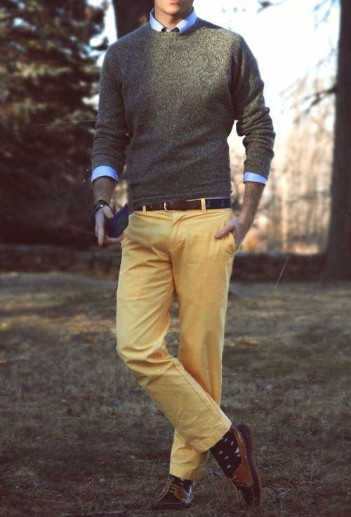student w swetrze i żółtych chinosach