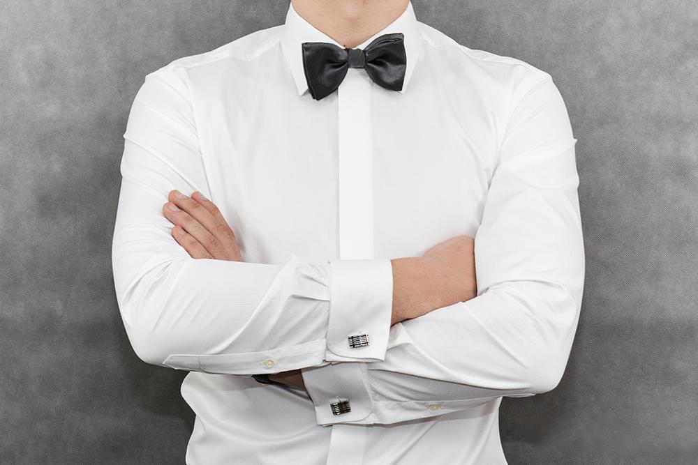 biała koszula z krytą plisą, czarna mucha i srebrne spinki do mankietów