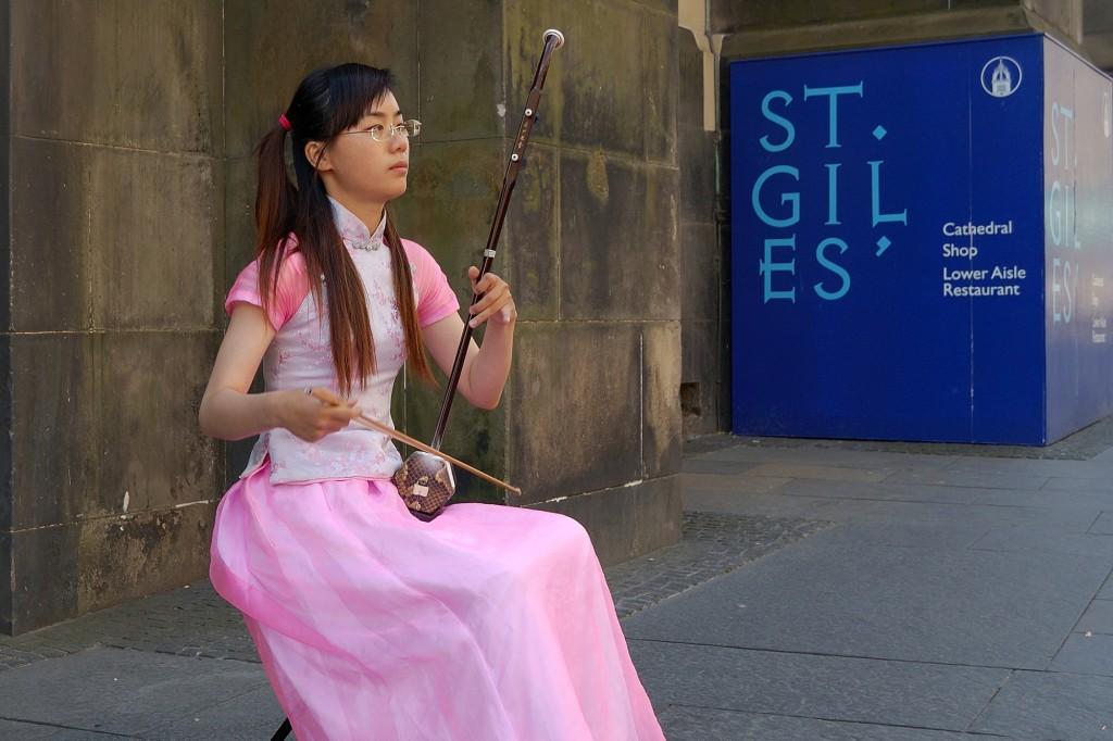 dziewczyna grająca na erhu pod katedrą św. Idziego