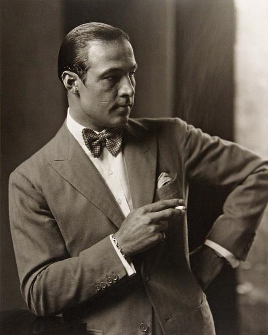 Rudolph Valentino w garniturze z muchą i papierosem w ręku
