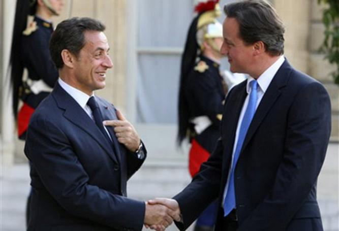 Nicolas Sarkozy przetrzymujący rękę premiera Wielkiej Brytanii Davida Camerona