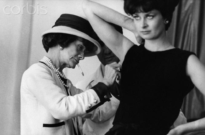 Coco Chanel poprawia sukienkę na modelce