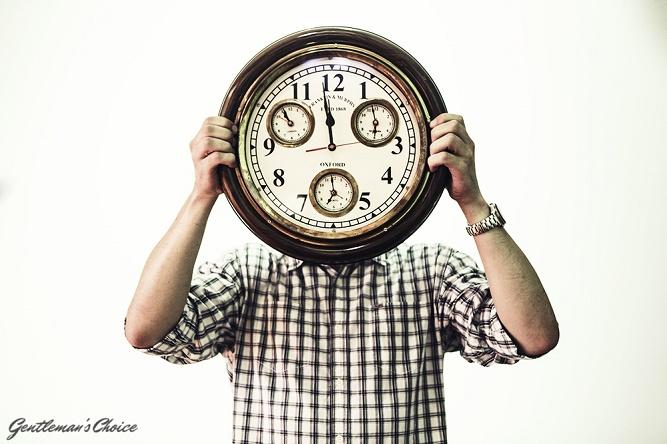 mężczyzna zasłaniający głowę zegarem