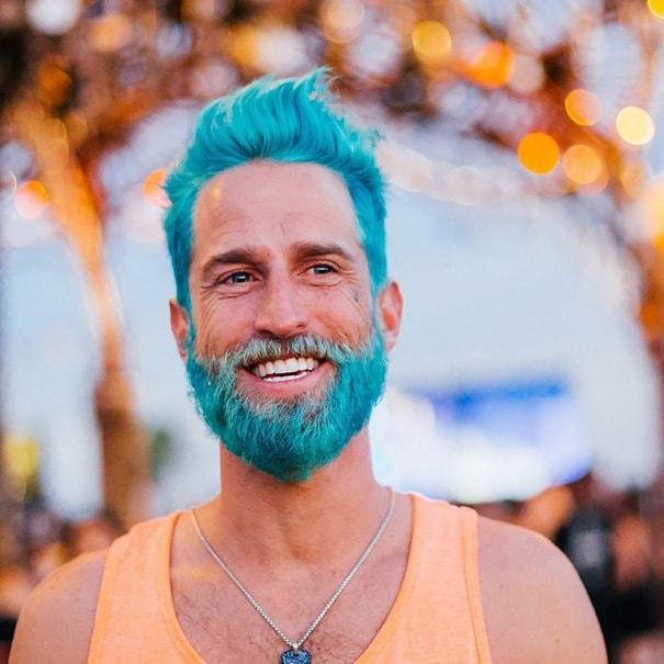 Mężczyzna z niebieskimi włosami i brodą.