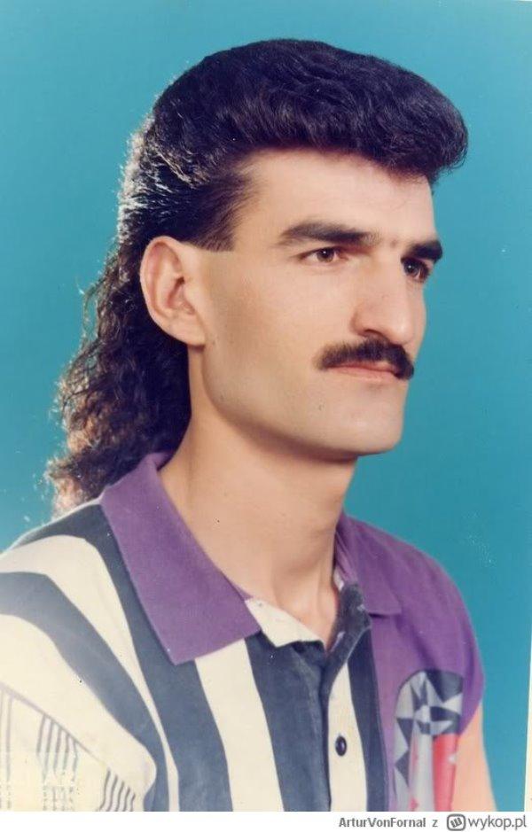 Mężczyzna z wąsem i długimi włosami z tyłu.